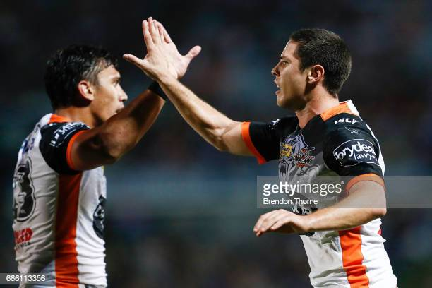 Mitchell Moses and Elijah Taylor of the Tigers celebrate during the round six NRL match between the North Queensland Cowboys and the Wests Tigers at...