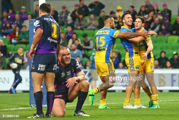 Mitchell Moses of the Eels is congratulated by his teammates after scoring a try as Nate Myles of the Storm looks on during the round 18 NRL match...
