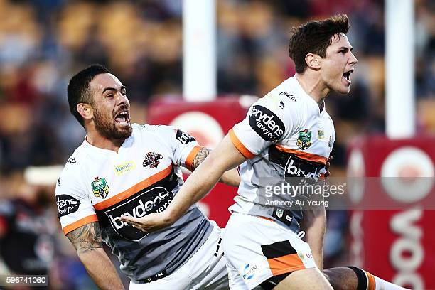 Mitchell Moses of the Tigers celebrates with teammate Dene Halatau after scoring a try during the round 25 NRL match between the New Zealand Warriors...