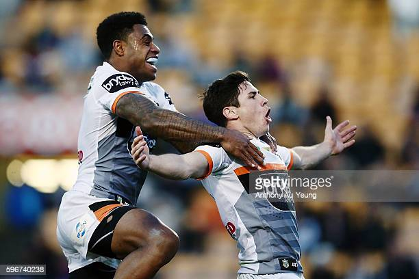 Mitchell Moses of the Tigers celebrates with teammate Kevin Naiqama after scoring a try during the round 25 NRL match between the New Zealand...