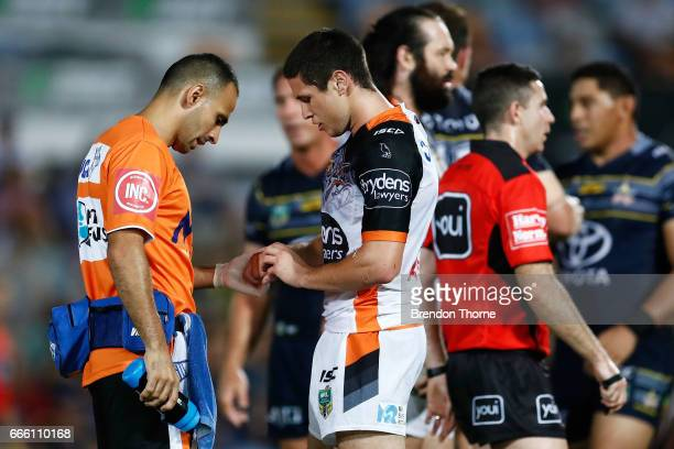 Mitchell Moses of the Tigers receives attention from a trainer during the round six NRL match between the North Queensland Cowboys and the Wests...