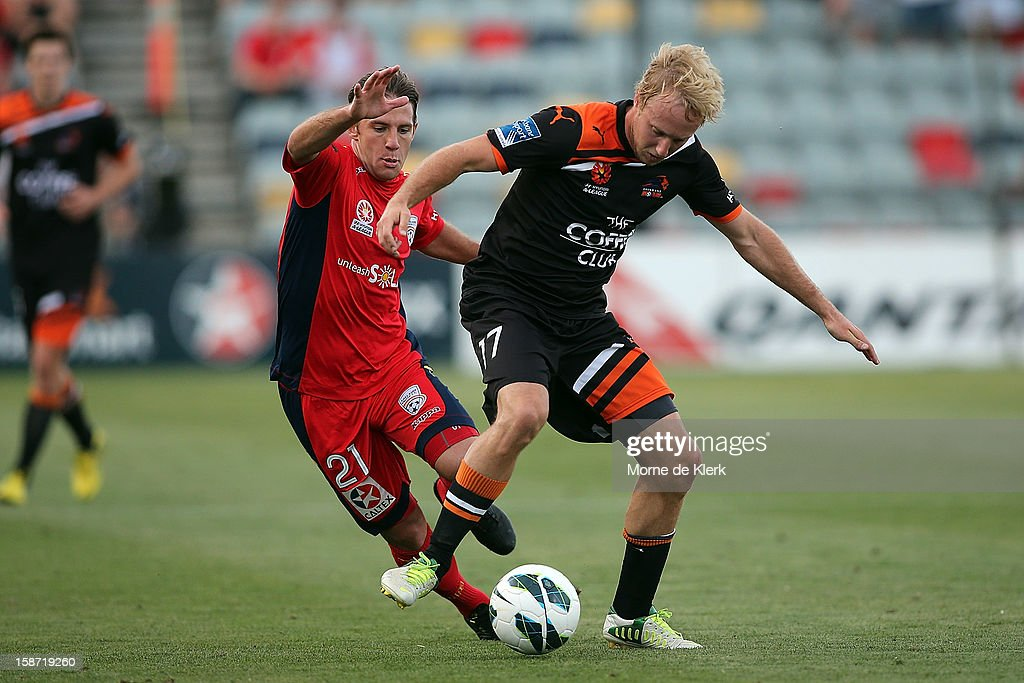 Mitchell Nichols of Brisbane is brought down by Jeronimo Neumann of Adelaide during the round 13 A-League match between Adelaide United and the Brisbane Roar at Hindmarsh Stadium on December 26, 2012 in Adelaide, Australia.