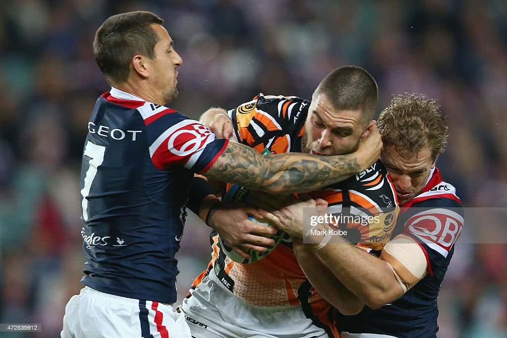 Mitchell Pearce and Jake Friend of the Roosters tackle Curtis Sironen of the Wests Tigers during the round nine NRL match between the Sydney Roosters and the Wests Tigers at Allianz Stadium on May 8, 2015 in Sydney, Australia.