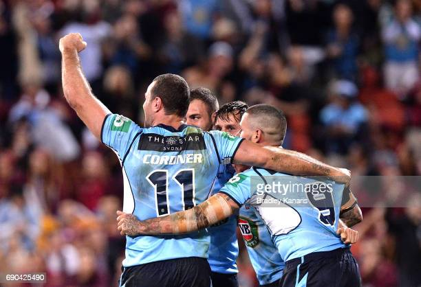 Mitchell Pearce of the Blues is congratulated by team mates after scoring a try during game one of the State Of Origin series between the Queensland...