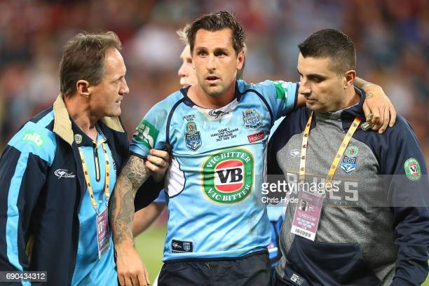 Mitchell Pearce of the Blues is helped from the field during game one of the State Of Origin series between the Queensland Maroons and the New South...