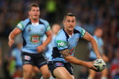 Mitchell Pearce of the Blues runs the ball during game three of the ARL State of Origin series between the New South Wales Blues and the Queensland...