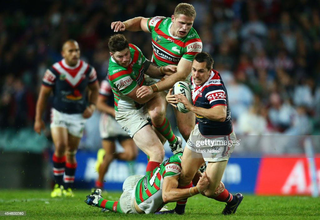 Mitchell Pearce of the Roosetrs is tackled during the round 26 NRL match between the Sydney Roosters and the South Sydney Rabbitohs at Allianz Stadium on September 4, 2014 in Sydney, Australia.