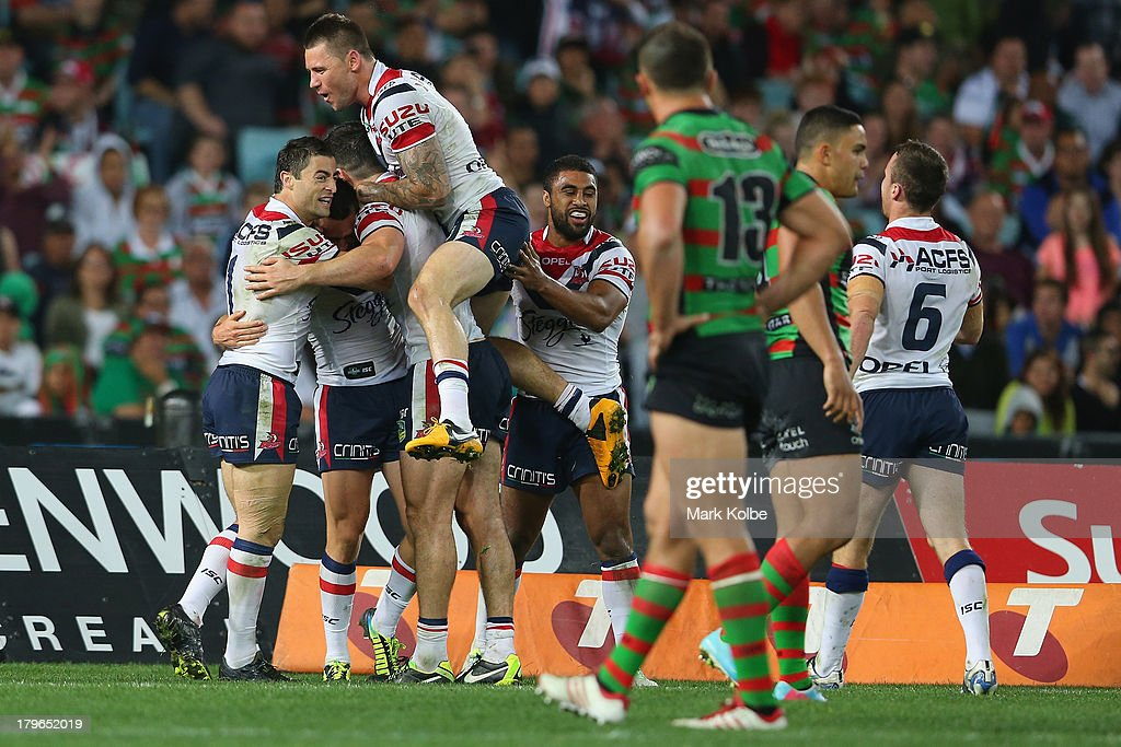 Mitchell Pearce of the Roosters celebrates with his team mates after he scored a try during the round 26 NRL match between the South Sydney Rabbitohs and the Sydney Roosters at ANZ Stadium on September 6, 2013 in Sydney, Australia.