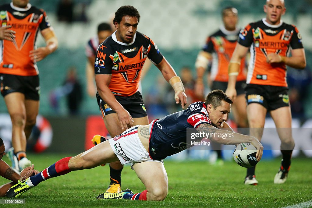 Mitchell Pearce of the Roosters reaches out to score a try during the round 23 NRL match between the Wests Tigers and the Sydney Roosters at Allianz Stadium on August 19, 2013 in Sydney, Australia.