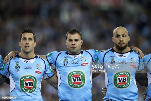 Mitchell Pearce Wade Graham and Blake Ferguson of the Blues stand and sing the National Anthem before game two of the State Of Origin series between...