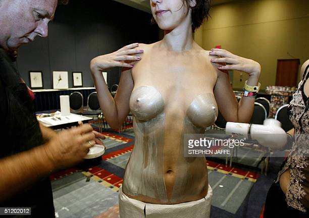 Mitchell Poulouin paints Shea Frola during an exhibition of body painting at the First International Nude Art Expo 21 August at the Washington...