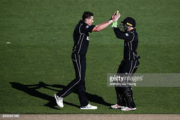 Mitchell Santner and Tom Latham of New Zealand celebrate taking the wicket of Pat Cummins of Australia during the first One Day International game...