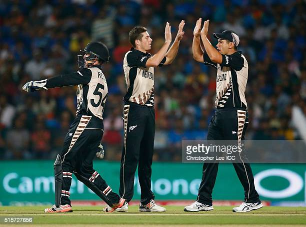Mitchell Santner of New Zealand celebrates taking the wicket of Rohi Sharma of India with Ross Taylor of New Zealand during the ICC World Twenty20...