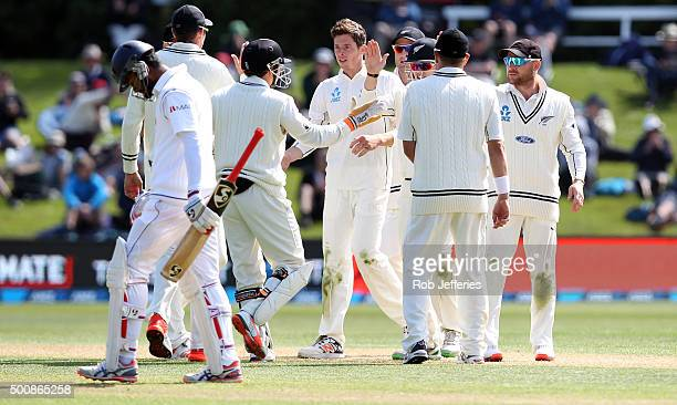 Mitchell Santner of New Zealand celebrates with his teammates after taking the wicket of Dimuth Karunaratne of Sri Lanka during day two of the First...
