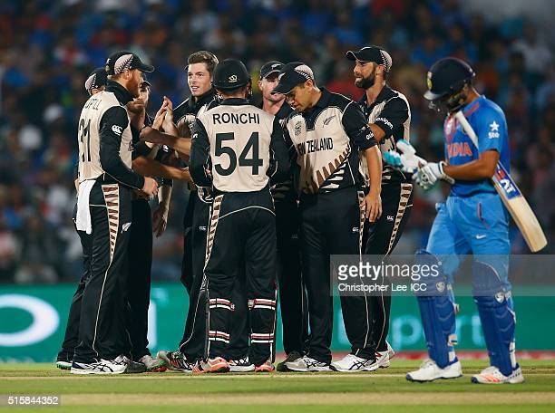 Mitchell Santner of New Zealand is congratulated by his team mates after he takes the wicket of Rohi Sharma of India during the ICC World Twenty20...