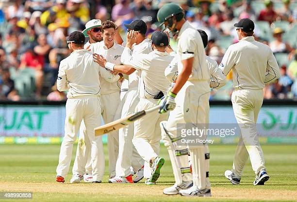 Mitchell Santner of New Zealand is congratulated by team mates after taking the wicket of Josh Hazlewood of Australia during day two of the Third...