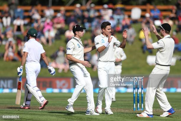 Mitchell Santner Trent Boult and Jimmy Neesham of New Zealand celebrate the dismissal of Stephen Cook of South Africa during day one of the First...