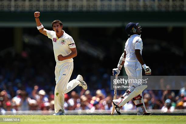 Mitchell Starc of Australia celebrates after taking the wicket of Mahela Jayawardene of Sri Lanka during day one of the Third Test match between...