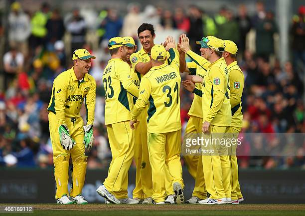 Mitchell Starc of Australia celebrates after taking the wicket of Josh Davey of Scotland during the 2015 Cricket World Cup match between Australia...