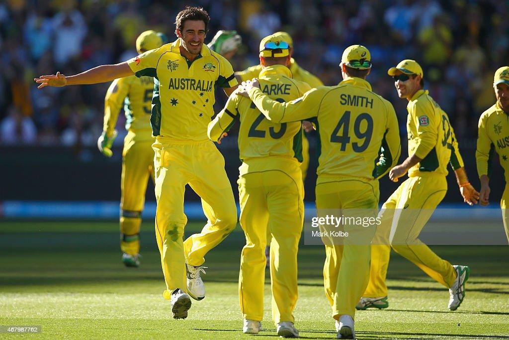 Mitchell Starc of Australia celebrates taking the wicket of Luke Ronchi of New Zealand as he runs to congratulate Michael Clarke of Australia who...