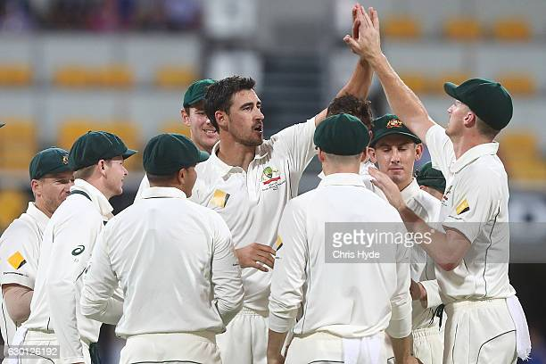 Mitchell Starc of Australia celebrates with team mates after dismissing Sami Aslam of Pakistan during day three of the First Test match between...
