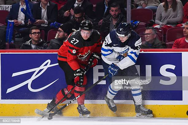 Mitchell Stephens of Team Canada and Janne Kuokkanen of Team Finland battle for the puck near the boards during the IIHF exhibition game at the Bell...