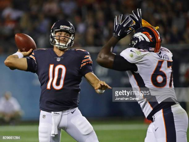 Mitchell Trubisky of the Chicago Bears passes under pressure from Shakir Soto of the Denver Broncos during a preseason game at Soldier Field on...