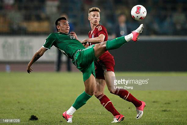 Mitchell Weiser of FC Bayern Muenchen challenges Mao Jianqing of Beijing Guoan during the Beijing Guo'an v Bayern Muenchen Friendly Match at Beijing...