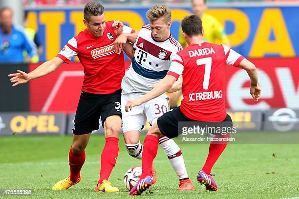 Mitchell Weiser of Muenchen battles for the ball with Christian Giuenther of Freiburg and his team mate Vladimir Darida during the Bundesliga match...