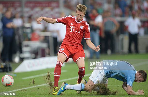 Mitchell Weiser of Muenchen is challenged by James Milner of Manchester during the Audi cup 2013 final between FC Bayern Muenchen and Manchester City...