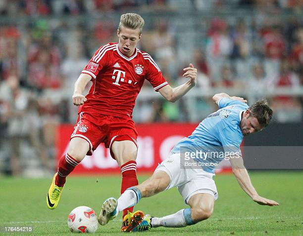 Mitchell Weiser of Muenchen is challenged by James Milner of Manchester during the Audi Cup 2013 final match between FC Bayern Muenchen and...