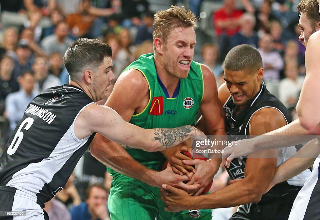 Mitchell Young of the Townsville Crocodiles and Nate Tomlinson and Garrett Jackson of Melbourne United compete for the ball during the round seven...
