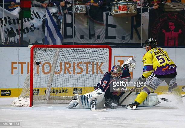 Mitja Robar of Krefeld Pinguine scores past Niklas Treutle of EHC Red Bull Muenchen during the DEL match between EHC Red Bull Muenchen and Krefeld...