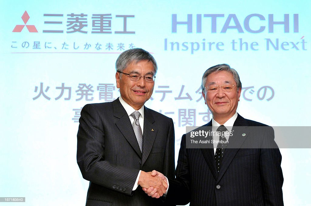 Mitsubishi Heavy Industries president and CEO Hideaki Omiya (L) and Hitachi president Hiroaki Nakanishi shake hands during a press conference on merger of their thermal power plant on November 29, 2012 in Tokyo, Japan.