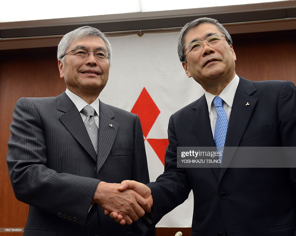 Mitsubishi Heavy Industries president Hideaki Omiya (L) shakes hands with executive vice president Shunichi Miyanaga as Miyanaga was named as the succesor of Omiya at a press conference at the company's headquarters in Tokyo on February 6, 2013. Omiya will become chairman of the company. AFP PHOTO / Yoshikazu TSUNO