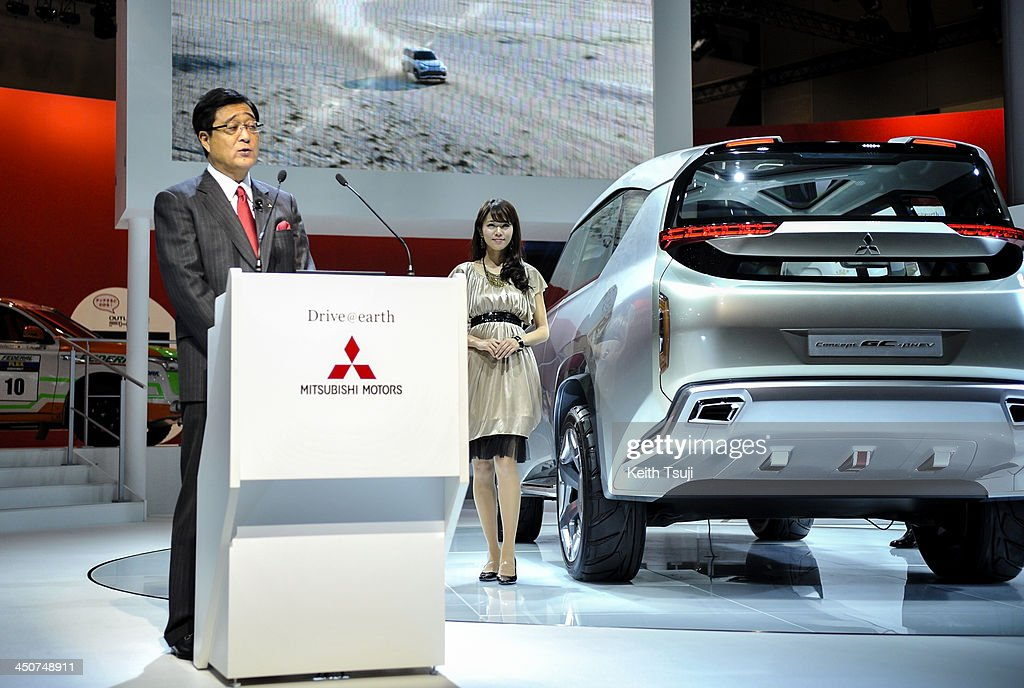 Mitsubishi Motors Corp president Osamu Masuko speaks by the company Concept GCPHEV vehicle during the press briefing at the Tokyo Motor Show 2013 at...