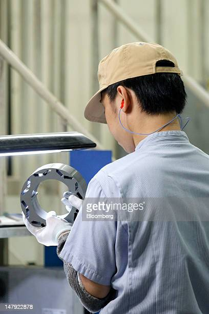 A Mitsui Hightec Inc employee makes a final inspection of a motor core used for Toyota Motor Corp's hybrid vehicles on the production line of the...