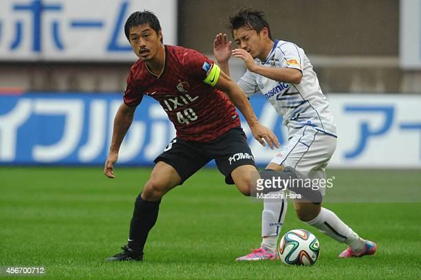 Mitsuo Ogasawara of Kashima Antlers and Hiroyuki Abe of Gamba Osaka compete for the ball during the JLeague match between Kashima Antlers and Gamba...