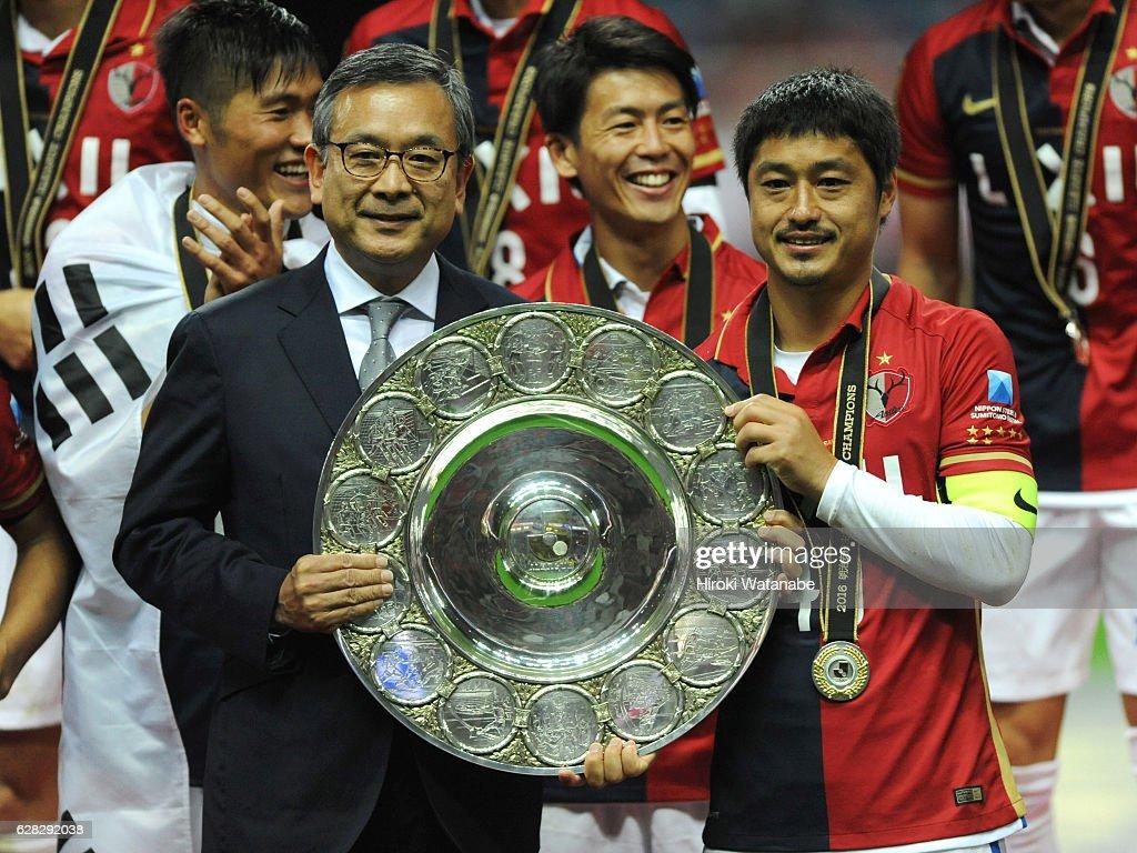 Mitsuo Ogasawara of Kashima Antlers and Mitsuru Murai hold up the trophy after the J.League Championship Final second leg match between Urawa Red Diamonds and Kashima Antlers at Saitama Stadium on December 3, 2016 in Saitama, Japan.