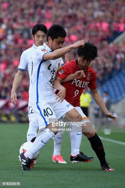 Mitsuo Ogasawara of Kashima Antlers and Yuki Muto of Urawa Red Diamonds compete for the ball during the JLeague J1 match between Urawa Red Diamonds...