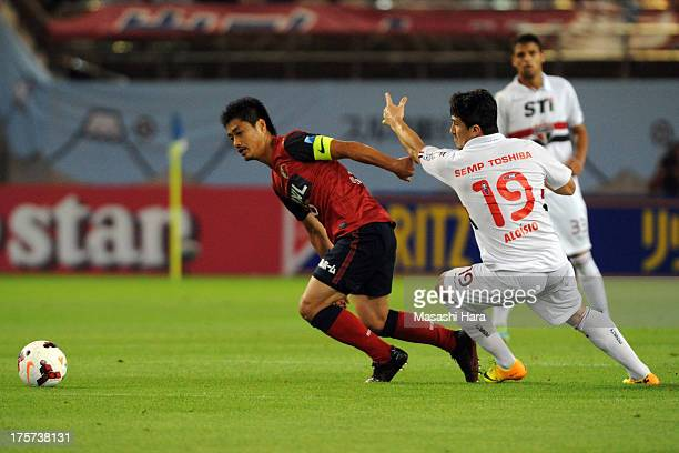 Mitsuo Ogasawara of Kashima Antlers competes for the ball with Aloisio of Sao Paulo FC during the Suruga Bank Championship match between Kashima...