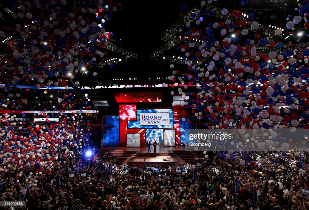 Mitt Romney, Republican presidential candidate, center right, and Representative Paul Ryan, vice presidential candidate, stand on stage while balloons fall at the Republican National Convention (RNC) in Tampa, Florida, U.S., on Thursday, Aug. 30, 2012. Romney, a wealthy former business executive who served as Massachusetts governor and as a bishop in the Mormon church, is under pressure to show undecided voters more personality and emotion in his convention speech tonight, even as fiscal conservatives in his own party say he must more clearly define his plans for reining in the deficit and improving the economy. Photographer: Scott Eells/Bloomberg via Getty Images