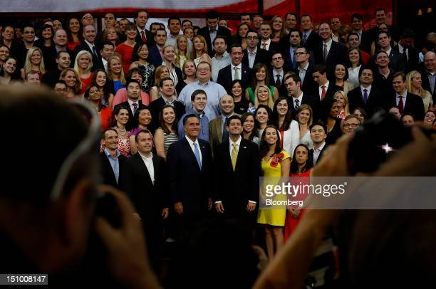 Mitt Romney Republican presidential candidate center smiles while standing beside Representative Paul Ryan vice presidential candidate during a group...