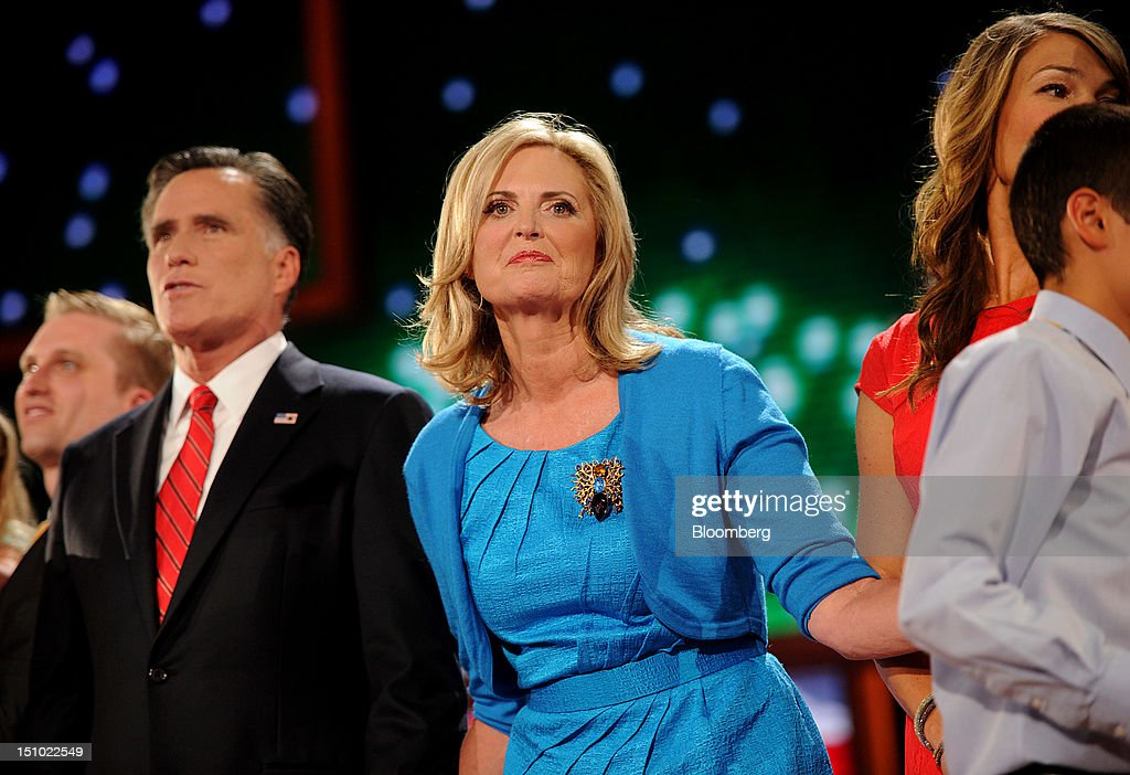 Mitt Romney, Republican presidential candidate, left, stands on stage with wife Ann Romney, center, at the Republican National Convention (RNC) in Tampa, Florida, U.S., on Thursday, Aug. 30, 2012. Republican presidential nominee Mitt Romney, a wealthy former business executive who served as Massachusetts governor and as a bishop in the Mormon church, is under pressure to show undecided voters more personality and emotion in his convention speech tonight, even as fiscal conservatives in his own party say he must more clearly define his plans for reining in the deficit and improving the economy. Photographer: Daniel Acker/Bloomberg via Getty Images