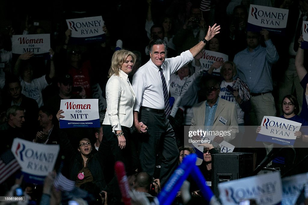 <a gi-track='captionPersonalityLinkClicked' href=/galleries/search?phrase=Mitt+Romney&family=editorial&specificpeople=207106 ng-click='$event.stopPropagation()'>Mitt Romney</a>, Republican presidential candidate, right, waves to the crowd as he arrives with wife <a gi-track='captionPersonalityLinkClicked' href=/galleries/search?phrase=Ann+Romney&family=editorial&specificpeople=868004 ng-click='$event.stopPropagation()'>Ann Romney</a> at a campaign rally at the Verizon Wireless Center in Manchester, New Hampshire, U.S., on Monday, Nov. 5, 2012. President Barack Obama beseeched core supporters and wayward backers to go to the polls, while Romney reached for an upset victory powered by anti-incumbent fervor on the final full day of a race that polls suggest has tilted slightly in the president's favor. Photographer: Andrew Harrer/Bloomberg via Getty Images