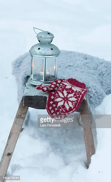 Mittens and lantern in snowy field