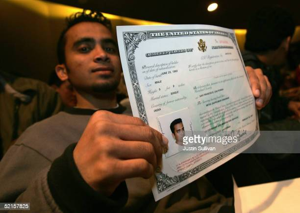 Mitul Chauhan displays his certificate of naturalization after being sworn in as a US citizen at a naturalization ceremony February 8 2005 in San...