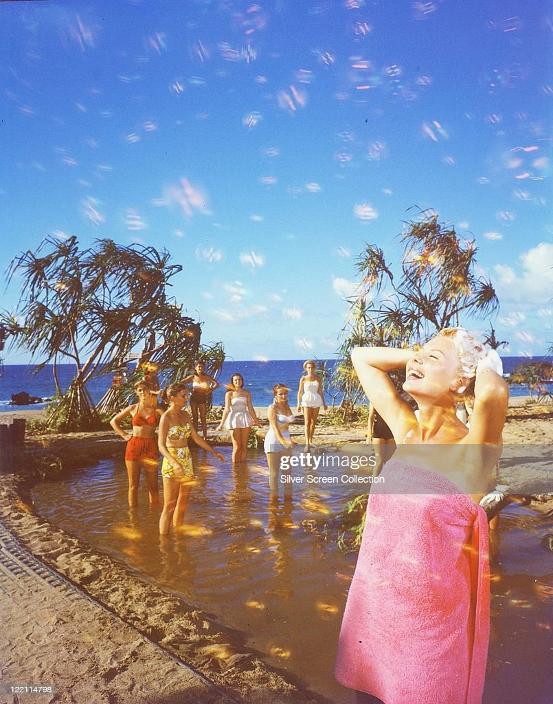 Mitzi Gaynor US actress singer and dancer wrapped in a pink towel showering with a group of women in a shallow pool in the background in a publicity...