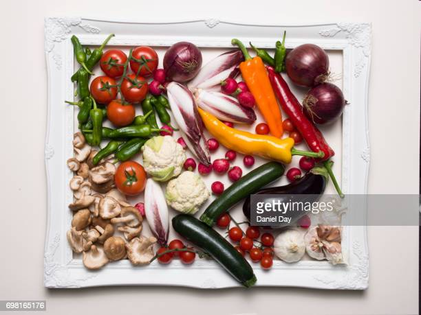 mix of different vegetables contained within a white picture frame on a white background