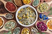 Mix of dried herbs on wooden spoons, top view. Horsetail, chamomile, cornflower, rose petals, nasturtium seeds, mullein, alchemilla, tilia, milk thistle seeds, sandalwood, fenugreek, calendula.